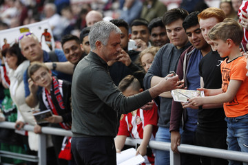Manchester United manager Jose Mourinho signs autographs for fans before the match