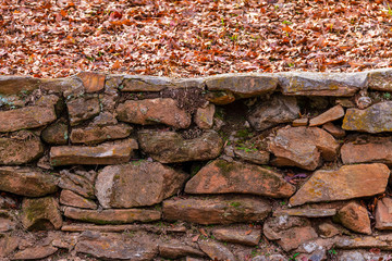 The rough stone wall and dry leaves in the autumn park.
