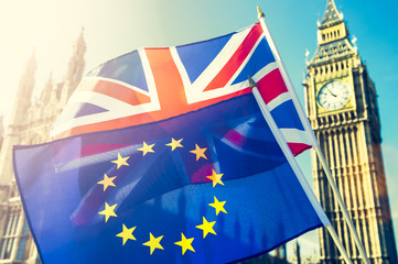 EU European Union flag and UK United Kingdom flag flying together in Brexit solidarity backlit by golden sun in front of the Houses of Parliament at Westminster in London