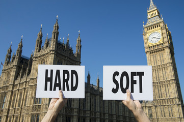 Hands holding signs with the words Hard and Soft, referring to the options of Brexit, the United Kingdom's exit from the European Union, in front of the Houses of Parliament at Westminster