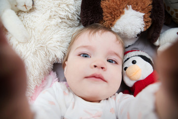 Funny baby girl taking photo of herself with favourite toys.