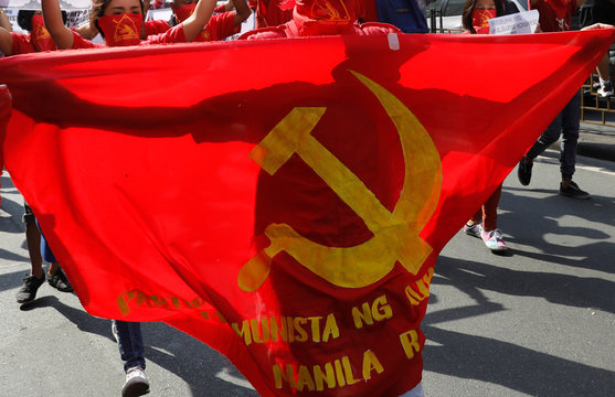 A protester is silhouetted behind a Communist sickle and hammer banner as members and supporters of an underground Communist movement march along a street in Manila