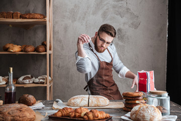 Concentrated man baker standing at bakery near bread