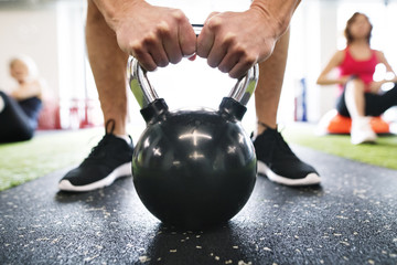Close-up of man exercising with kettlebell in gym