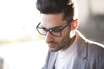 Attractive young man portrait with glasses and hard back light