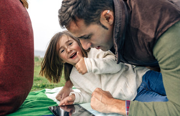 Happy girl and her father using tablet lying on blanket outdoors