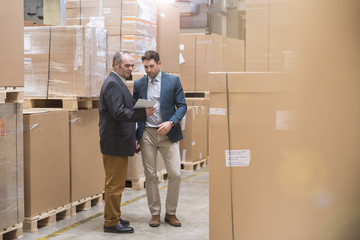 Two men looking at tablet in factory warehouse