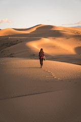 Rear view of a woman walking in desert during sunset