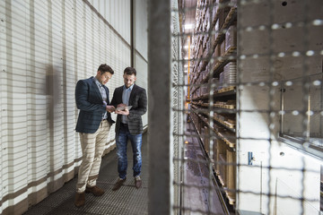 Two men in automatized high rack warehouse looking at tablet