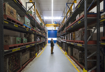 Businessman on the phone in factory storehouse