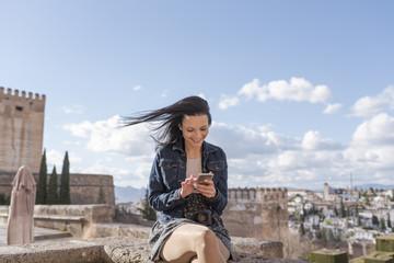Young woman looking smartphone in Granada, Spain.