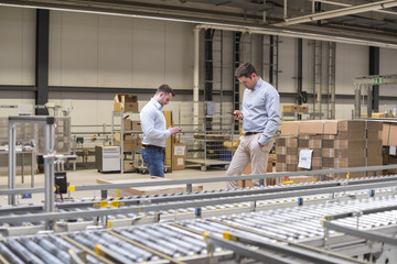Two men at conveyor belt in factory looking at cell phones