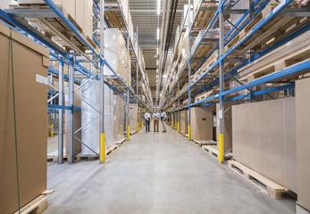 Three men standing in factory warehouse