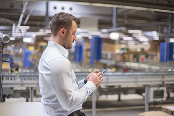 Man in factory looking at cell phone