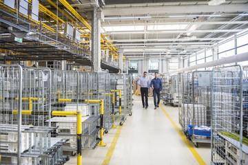 Two men walking in factory shop floor