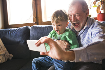 Grandfather and grandson sitting on couch,taking smartphone selfies