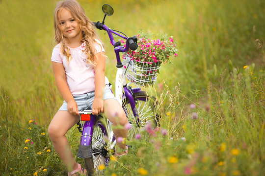 Little cute girl riding a bike with basket full of flowers. Cheerful child