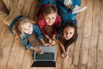 overhead view of little children using digital laptop at home