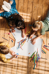 cute kids drawing on paper with pencils while lying on floor