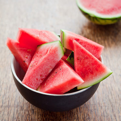 Fresh sliced red watermelon in bowl on rustic wooden background.