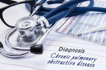 Diagnosis of Chronic pulmonary obstructive disease (COPD). On doctors table lies paper with title Chronic pulmonary obstructive disease surrounded by stethoscope, blood test results and thermometer