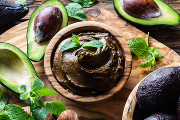 Avocado chocolate mousse on olive wooden board. Top view