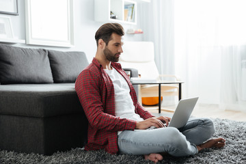 Man sitting indoors at home while using laptop computer