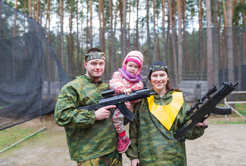 Portrait of family of three. Game in laser tag in the summer wood.