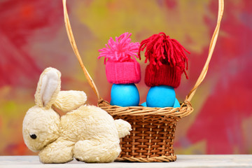 easter holiday, blue smurfs eggs in hats in basket, rabbit