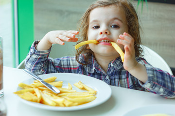 Little girl play with the french fries in a restaurant.