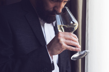man tasting a glass of white wine