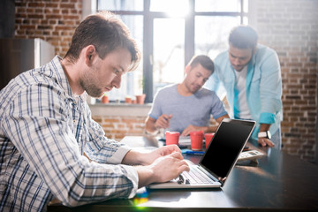 Young man using laptop while colleagues discussing project, small business meeting concept