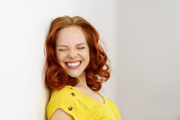 lachende frau macht die augen zu
