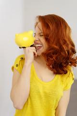 lachende frau hält ein gelbes sparschwein vor ihr gesicht