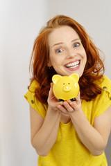 lachende frau zeigt ein gelbes sparschwein