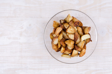 Fried young potatoes in the bowl above wooden background