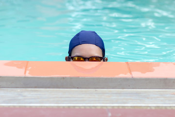 Woman in bathing cap peeking out of the water in the pool