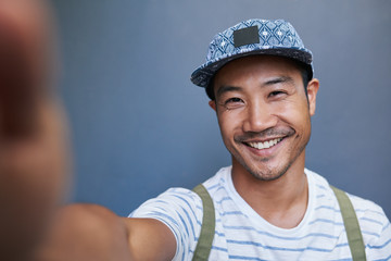 Stylish young Asian man taking a selfie outside