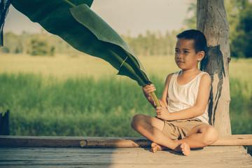 Portrait of boy holding banana leaf