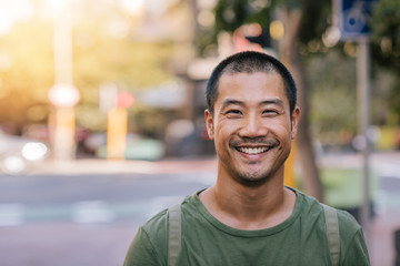 Young Asian man smiling confidently on a city street Fotoväggar
