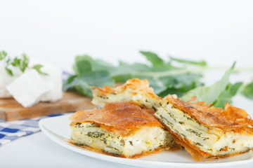 Homemade cheese and spinach pie on a white plate. Shallow depth of field.