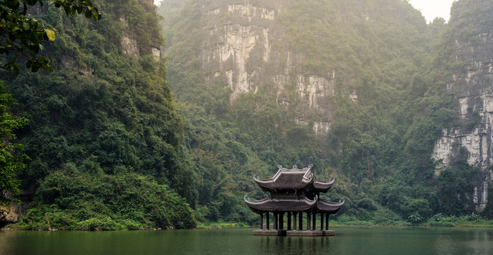 A scene of wooden bell tower floating on the water, surrounded by cliffs and jungle