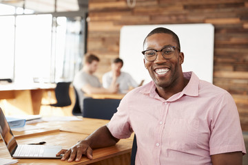 Young black man wearing glasses in office looking to camera