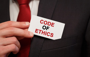 Businessman putting a card with text Code of Ethics in the pocket