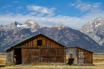 Small Wooden Barn and Outhouse Against Backdrop of Grand Tetons