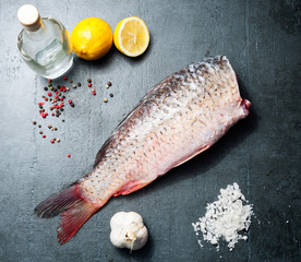Delicious fresh fish carp on dark vintage background for healthy food, diet or cooking concept, selective focus