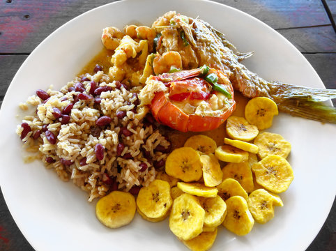 Local food. Lobster, red snapper fish, shrimp, rice, beans, fried plantains, coconut milk sauce. Roatan Honduras Creole unique traditional cuisine. Delicious seafood lunch, meal rustic wood background