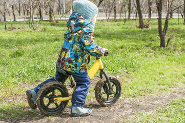 A little boy is riding in a park on a bicycle, a children's sport and an active lifestyle,run bike, balance bike