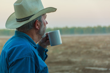 Senior contemplating field with coffee in morning
