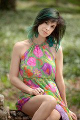 Pretty Woman With Teal Green Hair Sitting Outside in Flowered Dress